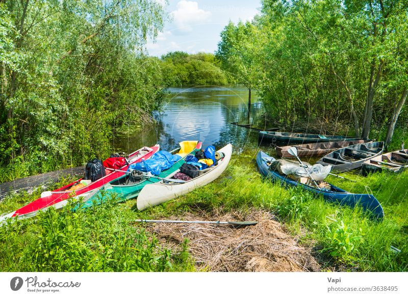 Many loaded kayaks with cargo on river boat water canoe trees activity summer vacation travel bags fishing boat bushes recreation kayaking leisure nature shore