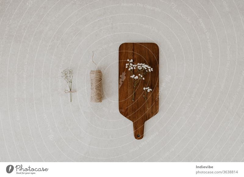 Chopping board with dried flower and string on marble background beige chopping board concept conscious consumption decoration craft decorative design diy