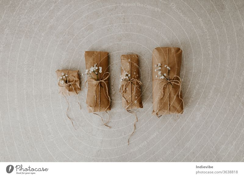 Four gift wrapped in paper with dried flower and string on marble background package wrapping holiday surprise reusable zero waste plastic free handmade minimal