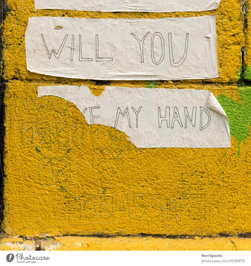 Will you take my hand? Graffiti adhesive tape hold hands by hand Ask torn down pasted embassy Wall (building) Wall (barrier) Characters Yellow incomplete