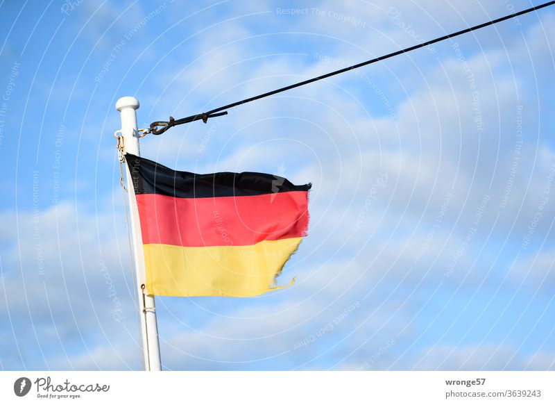 Frayed German flag fluttering in the wind on the mast of a ship under a blue sky Flag Germany German Flag Pole Bowmast Flagpole black red gold black-red-gold