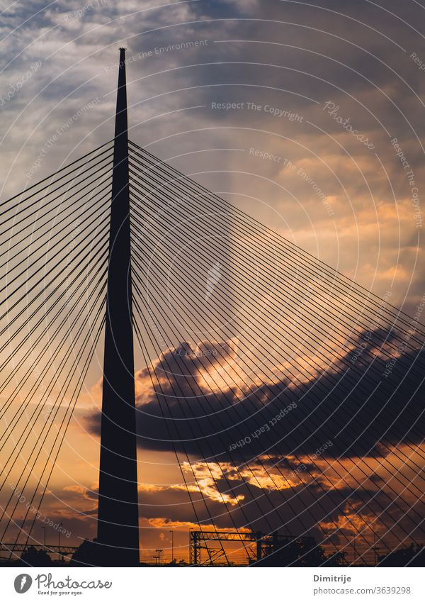 Big suspension bridge tower at sunset - sunrays through the clouds in the background modern architecture sky water steel city blue structure urban building