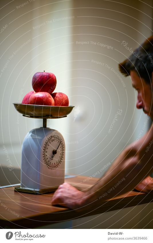 Man uses an old kitchen scale to determine the weight of a few apples Scale Weight read Reading figures kg Pound Display precise Accuracy fruit Preparation