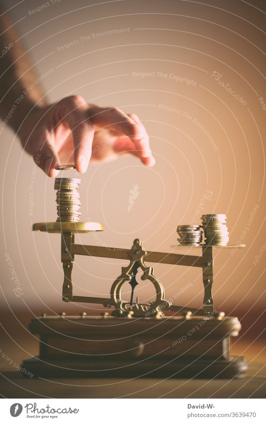Scales - man divides the coins fairly concept Dealers deal Neutral Background Copy Space top disequilibrium uneven difference share Deep depth of field Fairness