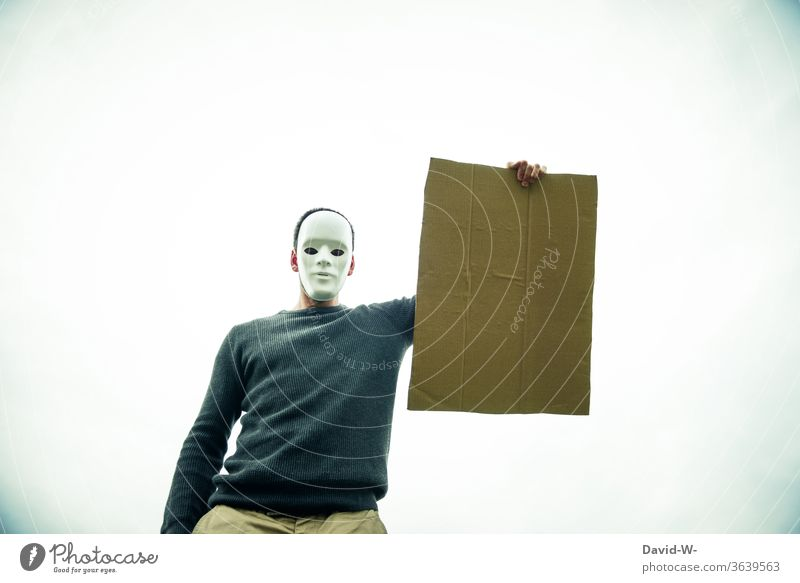 anonymous - masked man holds an empty cardboard sign in the air Cardboard Anonymous paperboard Mask anonymity cardboard box Man Clue indicative Safety point