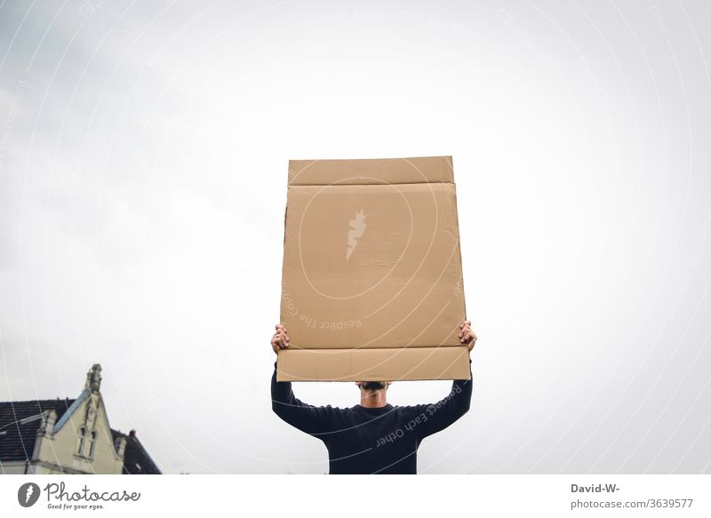 a man holds up a cardboard sign in the air and covers his face expression of opinion Freedom of expression observantly 1 Person Neutral background paperboard