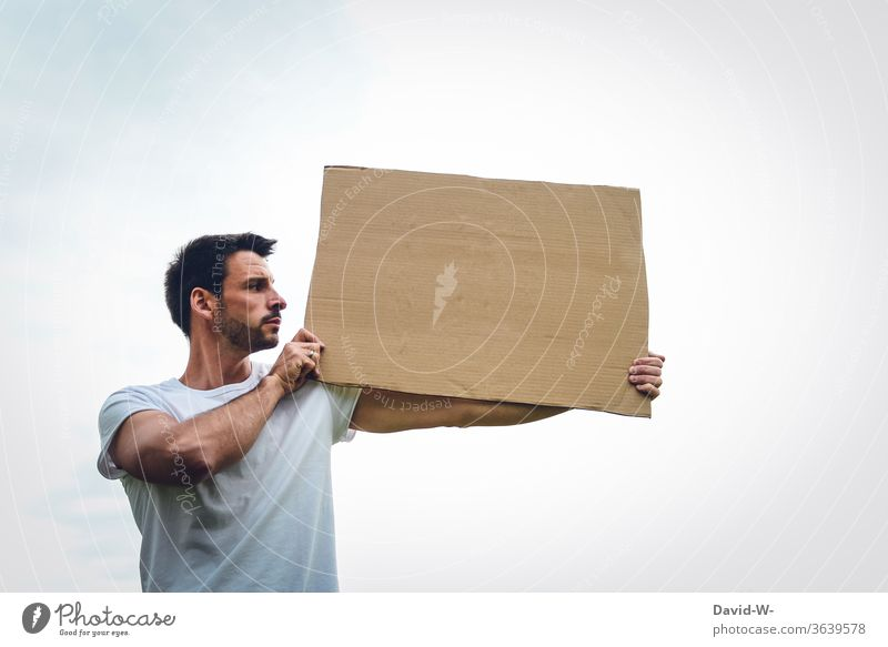 a person holds a cardboard sign in his hands, presents it and looks at what might be written there expression of opinion Freedom of expression observantly