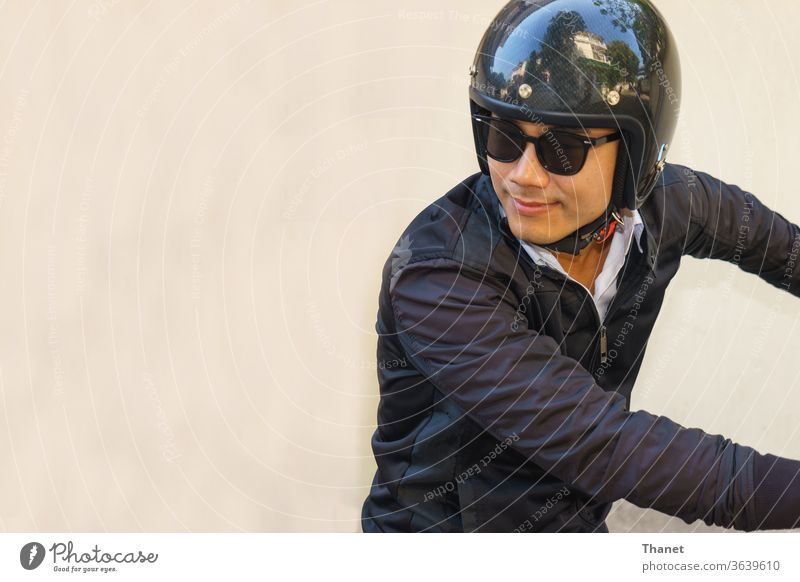 Young Asian motorcyclist wearing black jacket is looking back while riding his motorcycle. asian biker handsome helmet man motorbike rider sunglasses young