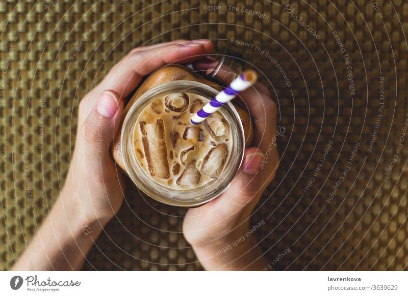Flatlay of mason jar with iced tea or coffee, selective focus beverage caffeine cold cool drink female fingers food hands healthy holding natural paper straw