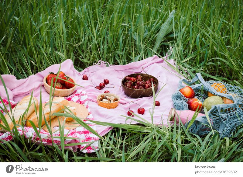 Zero waste summer picnic on the with cherries in the wooden coconut bowls, fresh bread and glass bottle of juice or smoothie on pink blanket, flatlay apples