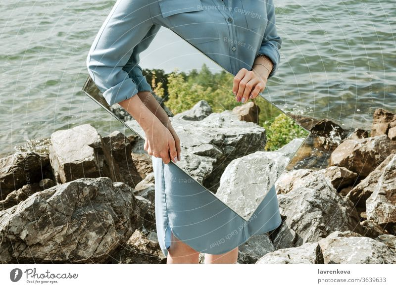 Closeup of woman standind on a shore in blue dress holding a mirror with trees and rocks reflection, selective focus adult clean concept environment faceless