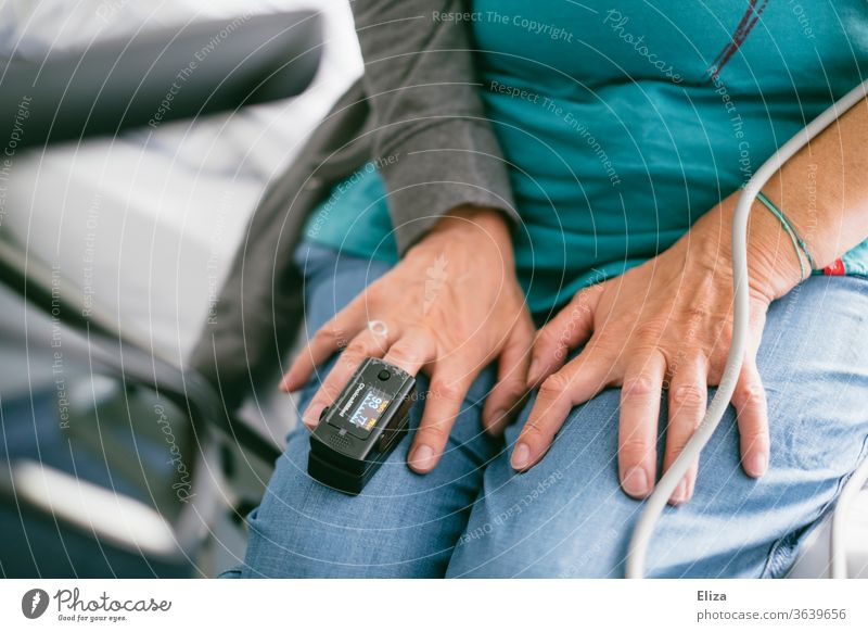 A woman in hospital with a pulse oximeter, to measure the pulse and oxygen saturation in the blood, on the middle finger Pulse Oximeter Measurement