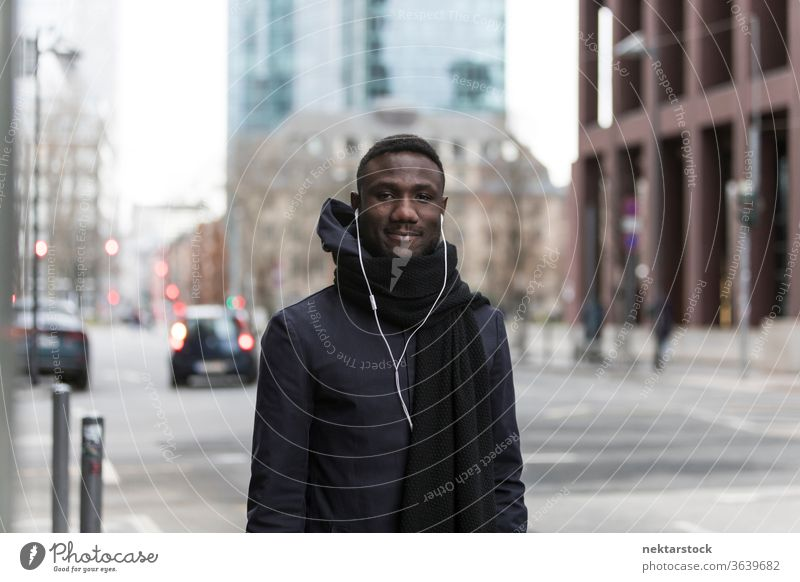 Handsome Black Man with Earphones Posing on Big City Street portrait earphones man African ethnicity smiling black coat autumn street listening music audiobook