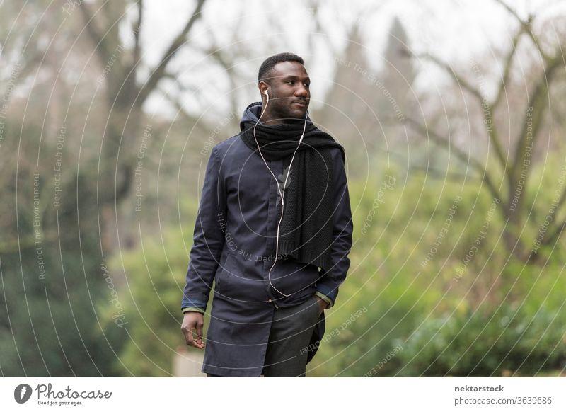 Handsome Black Man Walking in Park and Listening to Earphones portrait earphones man African ethnicity black public park listening music audiobook