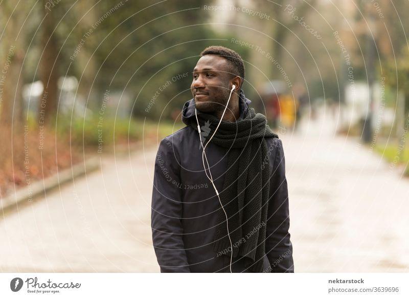 Young Black Man with Earphones Looking Away and Walking in Park portrait earphones man African ethnicity black public park listening music audiobook