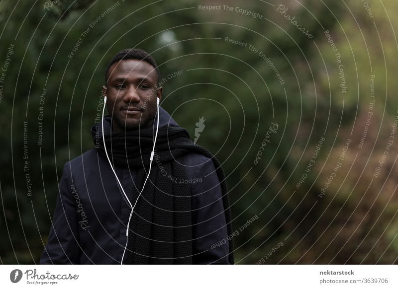 Young Man Listening to Audiobook in Park portrait earphones man African ethnicity black public park listening music audiobook real life model autumn young man