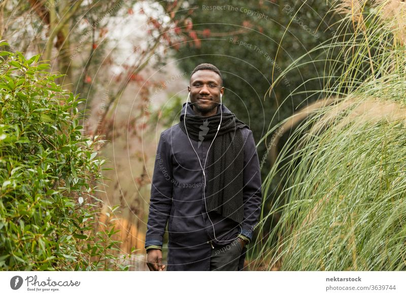 Happy Black Man with Earphones Posing in Park portrait earphones man African ethnicity black autumn leaf color grass tall public park listening music audiobook