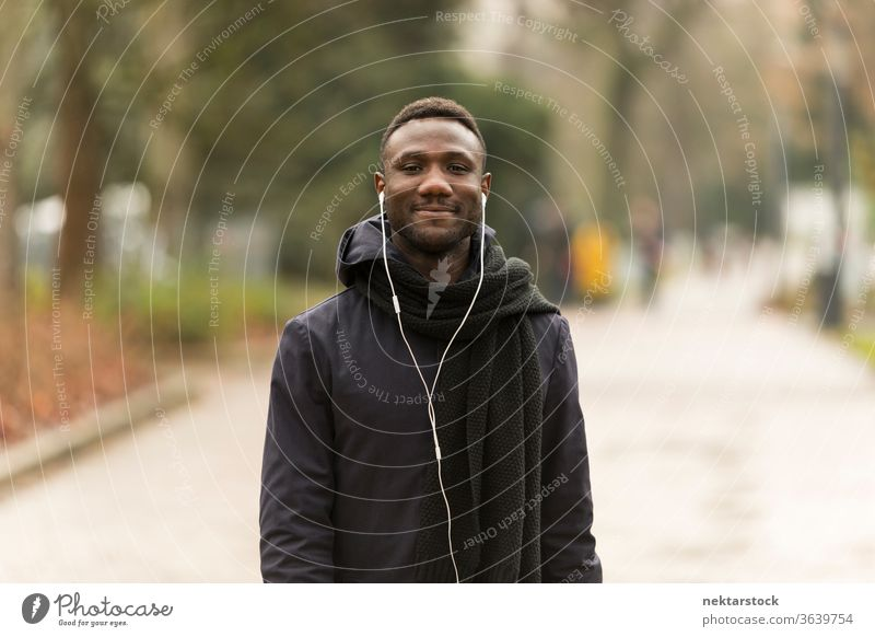 Young Man Listening to Earphones Smiling Confidently at Camera portrait earphones man African ethnicity black public park road trail listening music audiobook