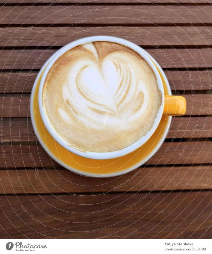 Yellow cup of coffe with milk on a dark background. Hot latte or Cappuccino decorated with foam with heart on a wooden table with copy space. Top view.