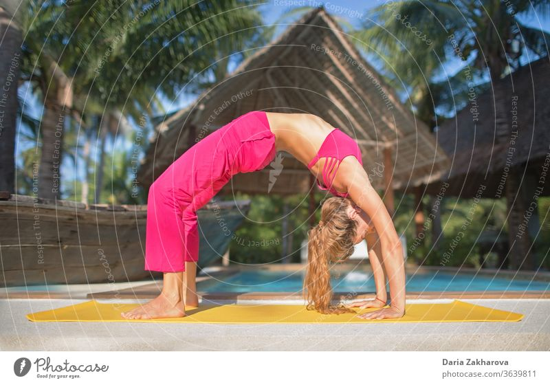urdhva dhanurasana.photo of the girl doing yoga by the pool in a resort woman young pose lifestyle balance fitness female health exercise workout training