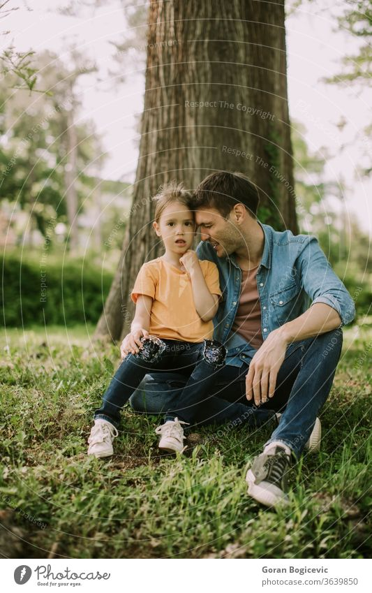 Single father sitting on grass by the tree with little daughter nature girl happy man park people family parent child kid love dad fun adult childhood summer