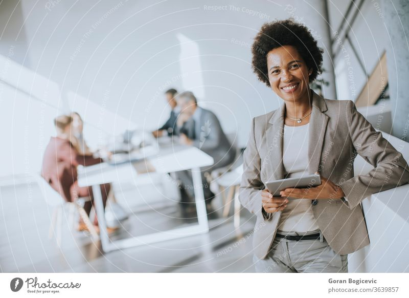 Young African American businesswoman standing using digital tablet in a modern office female black technology work young corporate african professional