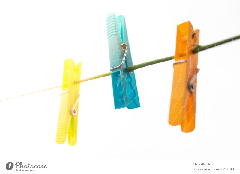 Three clothes pegs on a line against a white background Clothes peg three Clothesline Yellow Blue Orange White Neutral Background Light