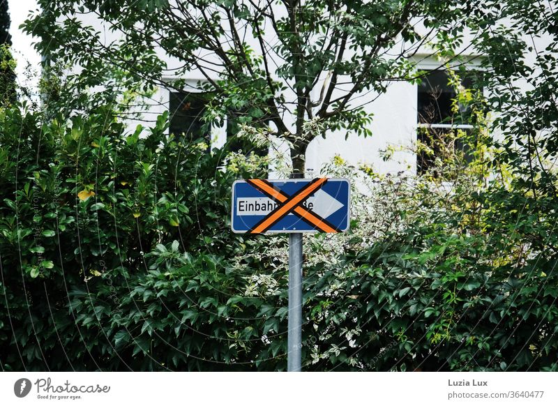A somewhat older one-way street sign is currently not needed and was therefore pasted in bright orange One-way street crossed out Whimsical Orange X