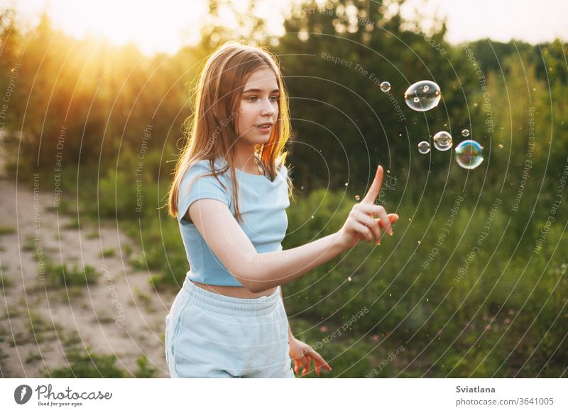 Cute girl with a beautiful smile catches soap bubbles on the background of a beautiful sunset. little blowing cute kid fun child childhood summer healthy pretty