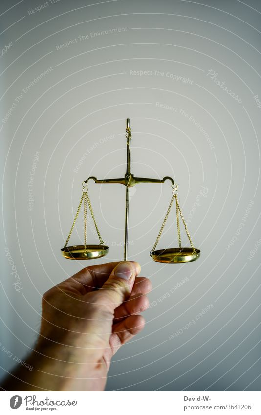 Hand holds a scale and compares both sides with each other Scale Time Money concept Balance Weight Fairness Honest Justice judiciary Lady Justice Detail