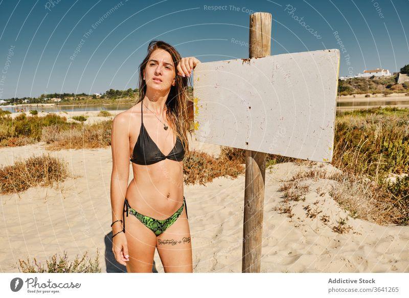 Cheerful female traveler in swimsuit on beach sea sign woman bikini tourism seafront vacation summer sand slim holiday swimwear coast cheerful nature seaside