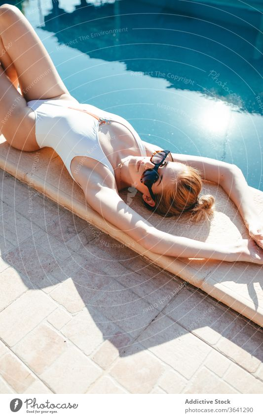 Slender woman in swimsuit relaxing at poolside sunbath tan vacation lying sunny female rest resort summer calm holiday chill swimwear water young weekend lady