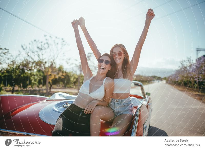 Delighted girlfriends having fun in summer on road vacation enjoy women cabriolet car carefree cheerful together holiday smile happy travel freedom nature