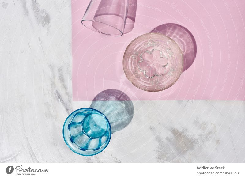 Set of glasses on pink table glassware set assorted shadow studio composition colorful crystal creative bright transparent shiny reflection object arrangement