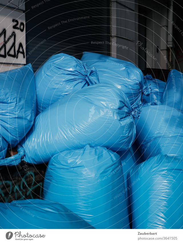 Blue plastic garbage bags are piling up on the street Garbage bag pile plastic foil Trash waste Stack Throw away Environment Waste management Recycling