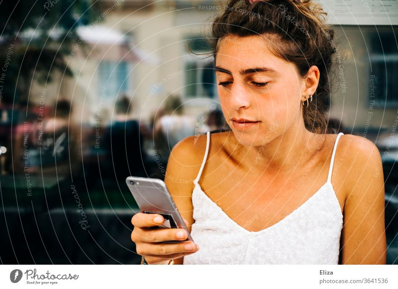 Young woman sitting outside in a café looking at her smartphone Sun mobile Reading employed Telephone girl concentrated Lifestyle Summer Summery already