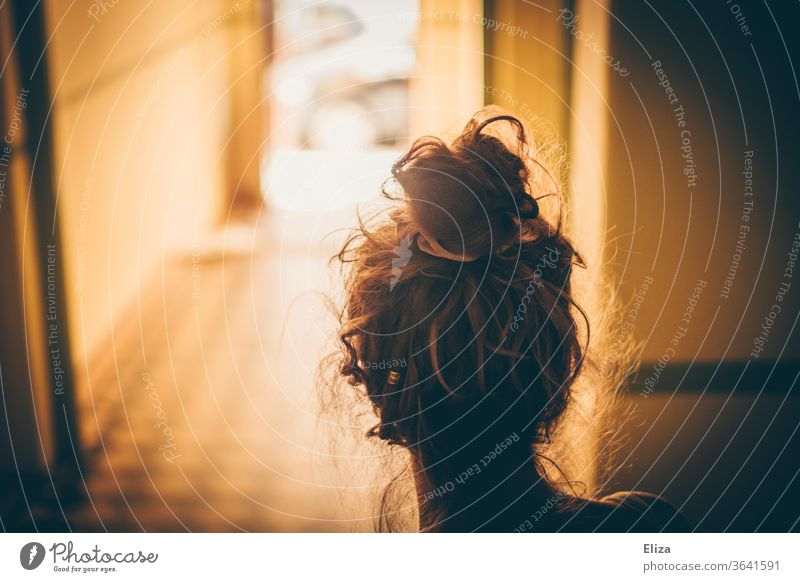 Young woman from behind in a hallway where the sun shines Chignon Going forsake sb./sth. Sun out sunshine off Divide call it a day leave home Loneliness door