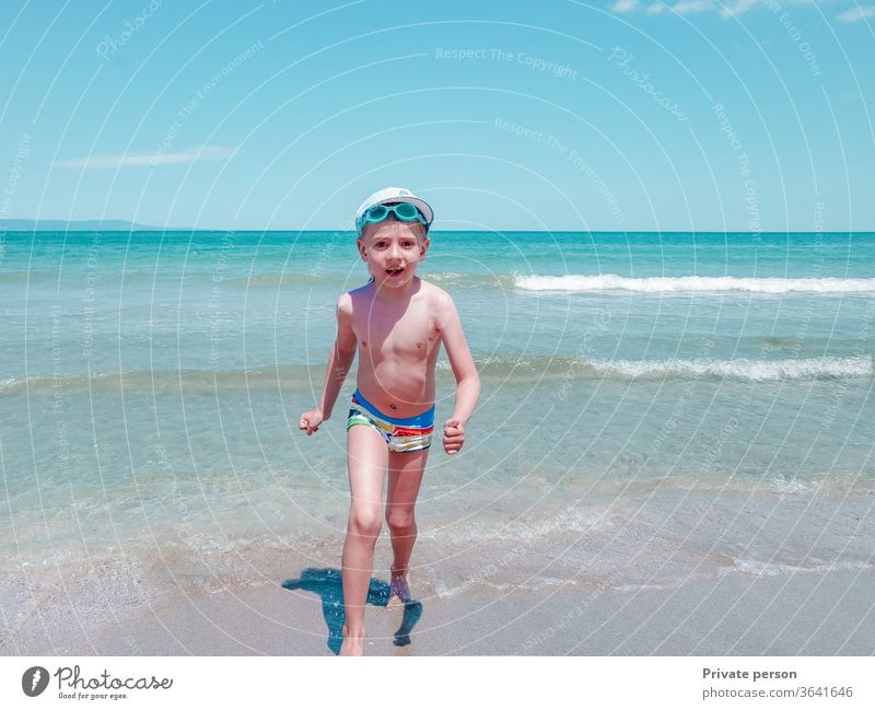 Happy little smiling boy runs along the seashore on a sunny summer day happy small beach sky blue young lifestyle sand outdoors beautiful cute one pretty hat