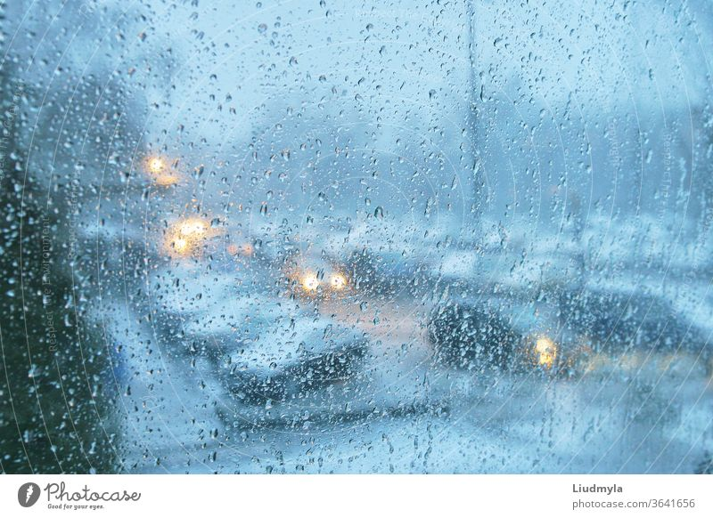 Rain drops on a transparent glass. Evening view of a city traffic. droplets cars jam vehicle transport glowing twilight storm street environment ride auto speed