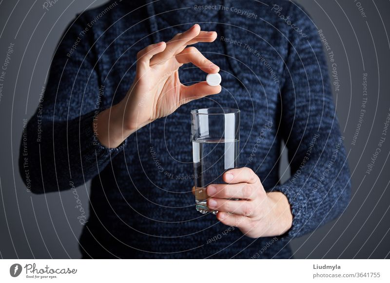 Male ready to dissolve the pill in water. Soluble white pill and a glass of water in his hands. Effervescent tablet aspirin in glass of water business young