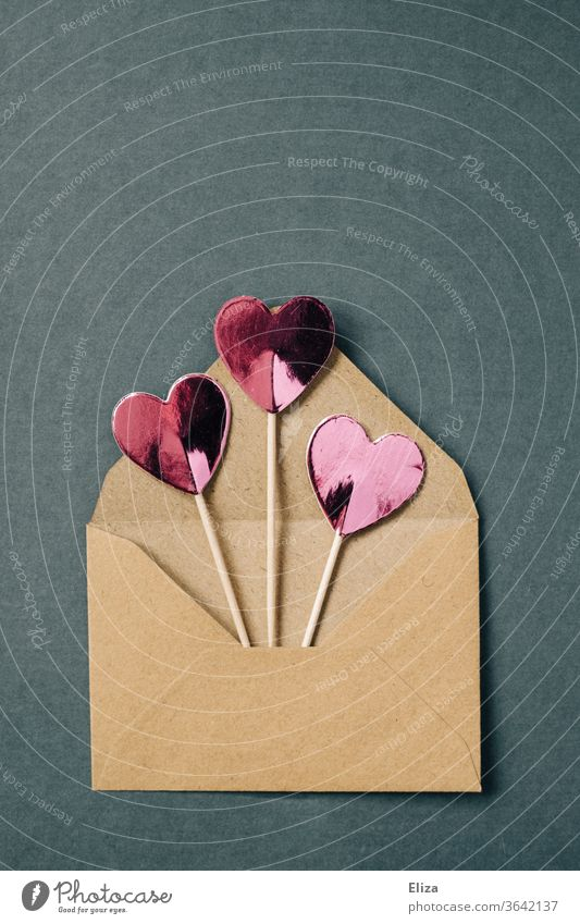 Three pink hearts on a stick peek out of a brown envelope Envelope (Mail) cuddle Best wishes Love Heart Love letter Communicate Copy Space top Letter (Mail)