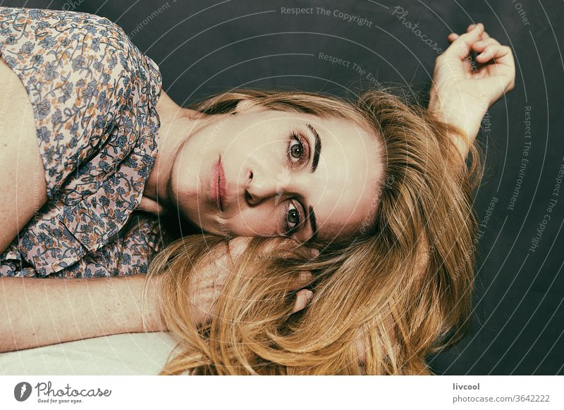mature woman lying on her side on her arm portrait adult beauty hair gesturing romantic attitude beautiful face hands dark background finger fiddling people