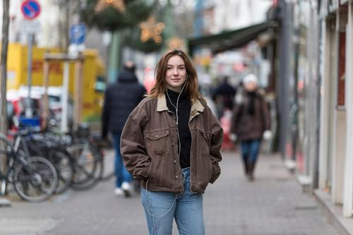 Young Woman in Jeans and Jacket Listening to Earphones on Sidewalk caucasian ethnicity woman female earphones audio music listening sidewalk street