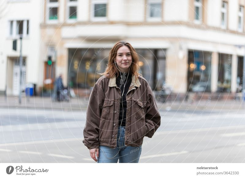 Young Woman with Genuine Smile Standing on City Street caucasian ethnicity woman female earphones audio music listening sidewalk street casual clothing smile