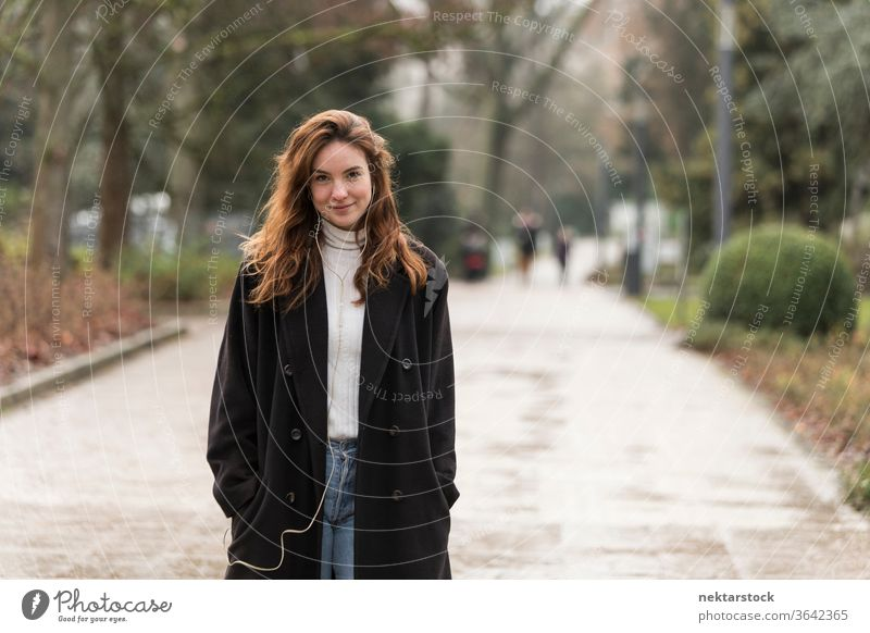 Beautiful Young Woman Smiling on Park Public Road caucasian ethnicity woman female earphones audio music listening brown hair real life model real person urban