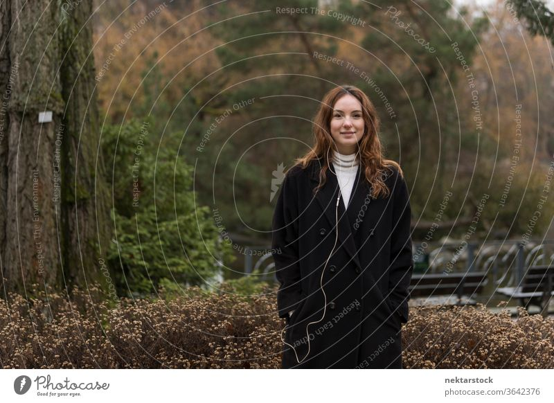 Young Caucasian Woman Posing in Autumnal Park caucasian ethnicity woman female earphones audio music listening brown hair real life model real person urban