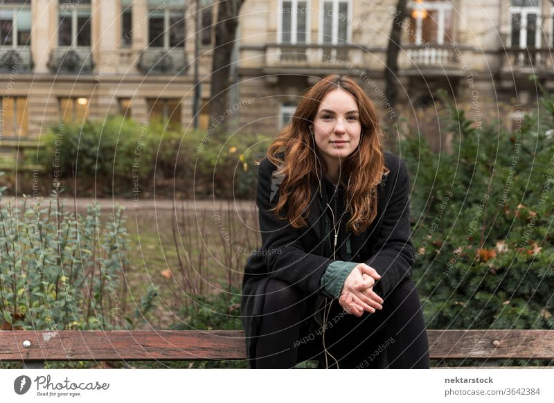 Young Woman Looking at Camera Seated on Bench caucasian ethnicity woman female earphones audio music listening brown hair real life model real person urban