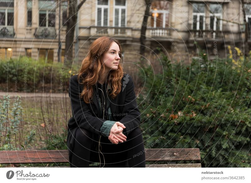 Young Caucasian Woman Sitting on Park Bench with Head Turned caucasian ethnicity woman female earphones audio music listening brown hair real life model