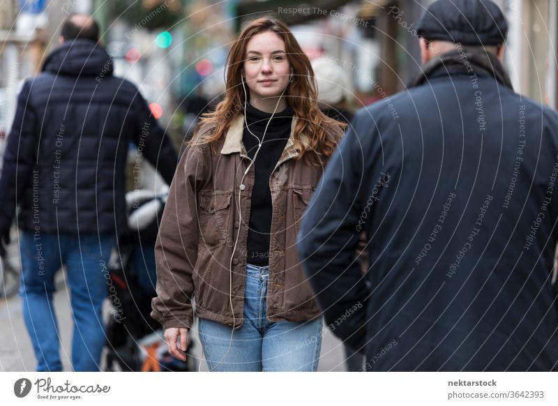 Young Woman Wearing Jeans and Brown Coat Walking Amongst Pedestrians caucasian ethnicity woman female earphones audio music listening sidewalk street