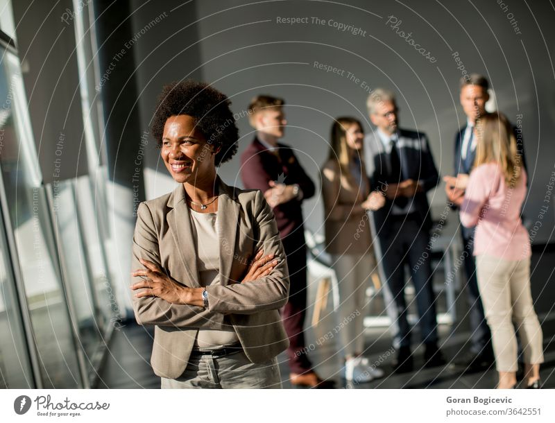 Professional black woman standing in office with folded arms and confident expression as other workers hold a meeting in background business teamwork career